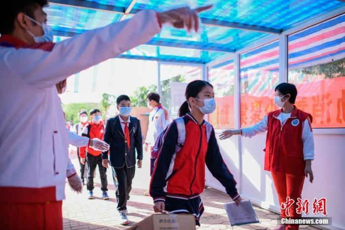 资料图:小学生通过体温检测通道进入校园。中新社记者 佟郁 摄