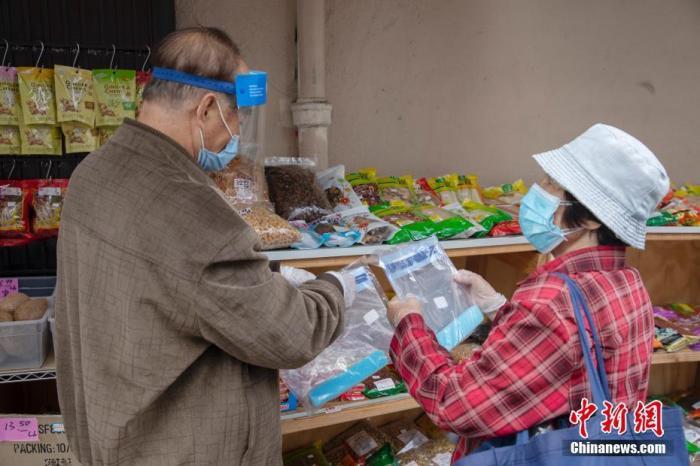 当地时间5月18日,一位老人在美国旧金山华埠一处店铺外的摊位前购买防疫物品。<a target='_blank' href='http://utino.cn/'>中新社</a>记者 刘关关 摄