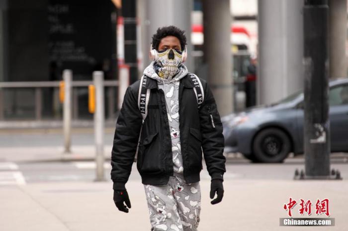 """当地时间5月19日,加拿大多伦多市中心,一名年轻人佩戴""""个性""""口罩走在街头。 <a target='_blank' href='http://htkgfwz.817psb.com/'>中新社</a>记者 余瑞冬 摄"""