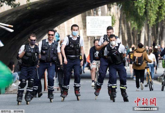 """5月11日,法国开始逐步""""解封"""",结束已经持续55天的全国""""封城""""状态。当地时间5月13日,法国巴黎,塞纳河沿岸警察穿着旱冰鞋巡逻。"""