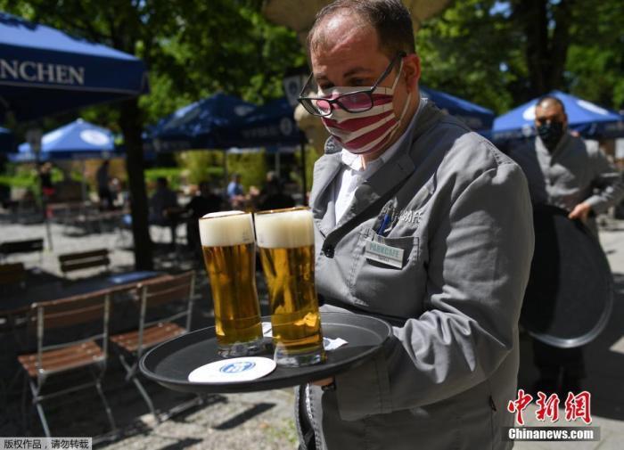 资料图:德国慕尼黑一家啤酒店重新开业后,顾客在户外推杯换盏,服务员佩戴口罩上岗。