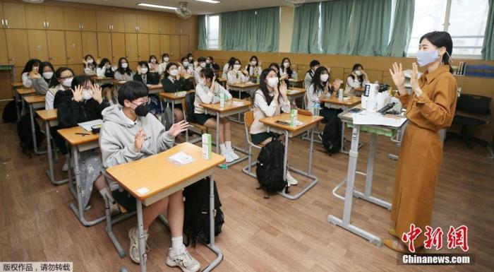 复课首日,仁川市某中学出现2个确诊病例,当地超过60所高中宣布暂停复课。此前,仁川一位培训机构老师确诊后隐瞒身份,引发交叉感染。图为韩国济州老师在课堂上与学生们相互问候。