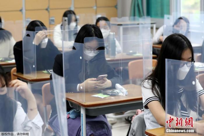 当地时间5月20日,韩国高三学生复课,韩国大田一所学校的课桌上安装了塑料挡板以防止病毒传播。