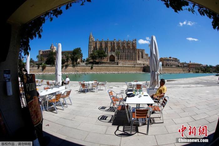 西班牙马略卡岛帕尔马市,一名男人在马略卡岛帕尔马大教堂四周的酒吧外喝啤酒,跟着西班牙疫情得以有效节制,部门餐厅酒吧规复营业,固然堂食处事还未从头开放,但能坐在户外吹着风喝一杯,已经相当惬意。