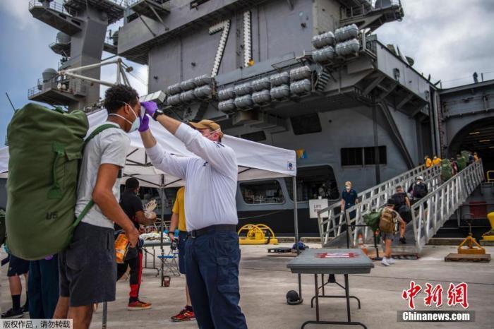 """因暴发新冠疫情停靠在关岛近两个月后,""""罗斯福""""号航空母舰于5月20日首次出海。图为船员在登舰前接受检查。"""