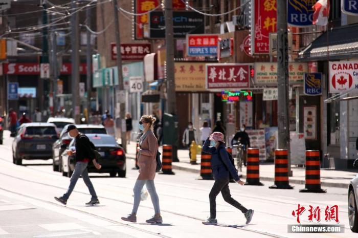 资料图:当地时间5月20日,佩戴着口罩的行人穿行在加拿大多伦多中区唐人街。加拿大累计报告新冠肺炎确诊病例在当日突破8万例,加公共卫生部门也在当日首度明确表示,建议民众在公共场合无法与他人保持安全社交距离的情况下佩戴非医用口罩。 /p中新社记者 余瑞冬 摄