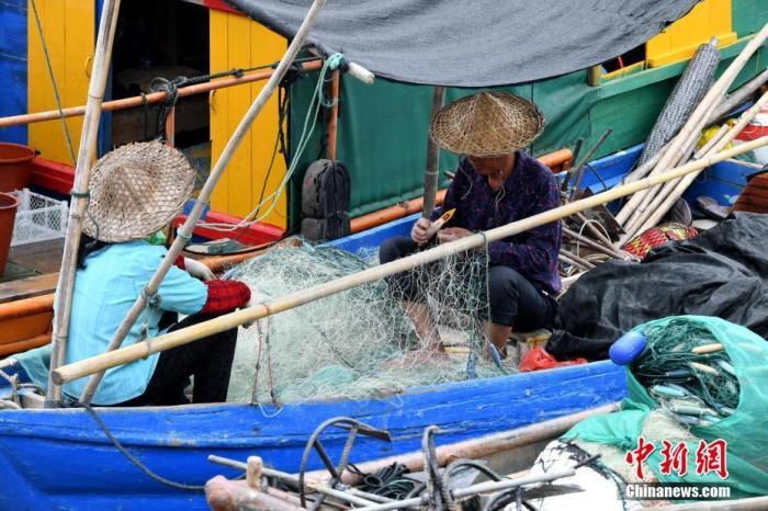 资料图:福建省福安市下白石镇下岐村村民在渔船上编织渔网。 中新社记者 王东明 摄