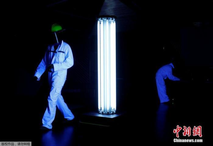 """当地时间5月20日,受新冠肺炎疫情的影响,新加坡的一家商场启用了新帮手——""""紫外线机器人""""。图为工作人员在测试""""紫外线机器人""""的消杀工作进展。"""