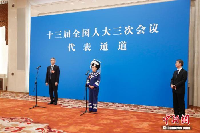 """5月22日,第十三届全国人民代表大会第三次会议在北京人民大会堂举行首场""""代表通道""""采访活动。图为全国人大代表罗杰(左)、石丽平(中)通过网络视频方式接受采访。 记者 杜洋 摄"""