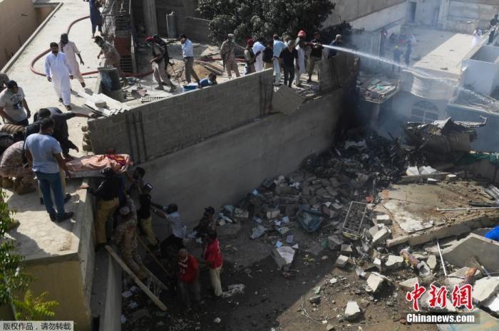 当地时间5月22日,巴基斯坦国际航空公司的一架飞机在卡拉奇的一个居民区坠毁,救援人员正在往飞机残骸上喷水。据报道,巴基斯坦国际航空公司(PIA)一架拉合尔飞往卡拉奇的PK8303客机在该国南部卡拉奇市郊居民区附近坠毁,机上载有100人左右。图为救援现场。