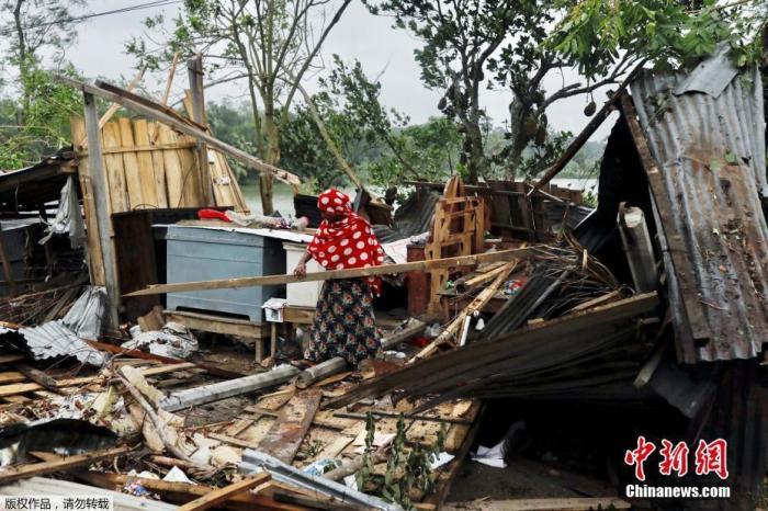 """当地时间5月21日,孟加拉国萨特赫拉,一名妇女在清理被气旋风暴""""安攀""""摧毁的房屋。"""