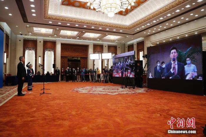 """5月22日,第十三届全国人民代表大会第三次会议在北京人民大会堂举行首场""""代表通道""""采访活动。图为全国人大代表罗杰、石丽平通过网络视频方式接受采访。 记者 杜洋 摄"""