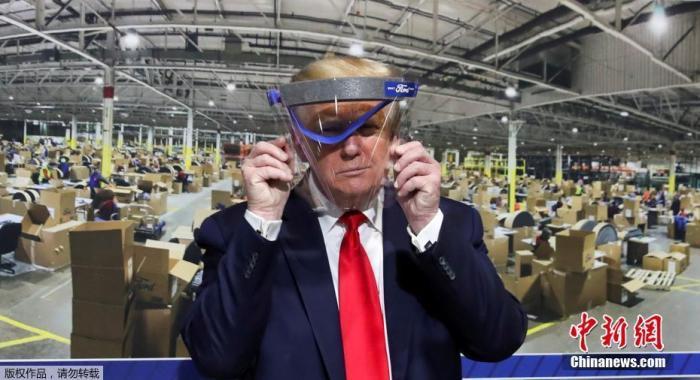 图为美国总统川普手举防护面具。