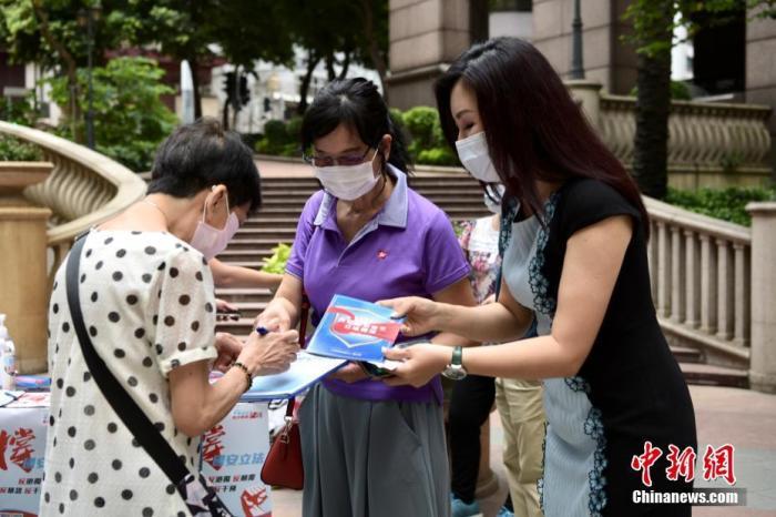 """5月24日上午,市民纷纷来到街站签名支持。""""香港各界撑国安立法联合阵线""""于香港各区多个街站进行签名行动,位于上环新纪元广场的街站,有市民前来签名支持。 记者 李志华 摄"""