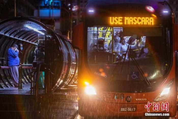 图为巴西公共交通上的民多戴着口罩乘车。