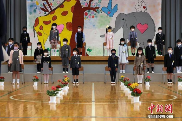 5月24日,日本山梨县一所小学举行新生入学仪式,新生们戴着口罩参加开学典礼。