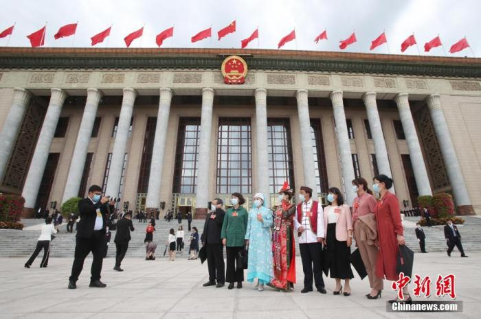 5月25日,十三届全国人大三次会议在北京人民大会堂举行第二次全体会议。图为部分参会代表在会后合影。 中新社记者 韩海丹 摄