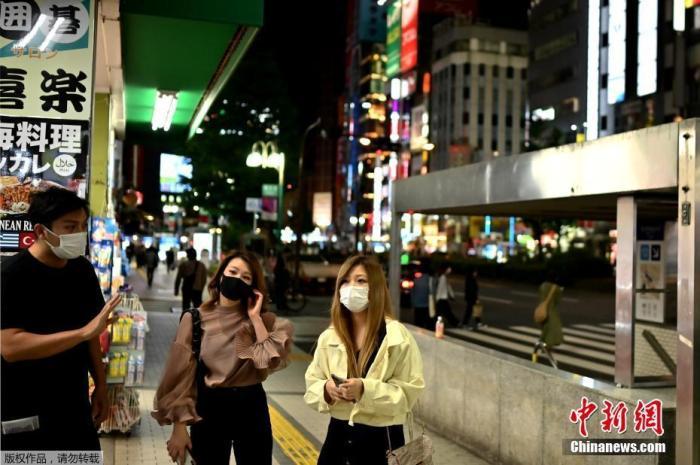。图为当地时间5月25日,东京新宿区,戴口罩的人们穿过街道。
