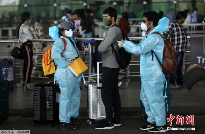 5月25日,在印度孟买希拉吉国际机场,旅客们穿戴着防护服和面罩出行。 印度政府允许国内航线自5月25日起恢复。