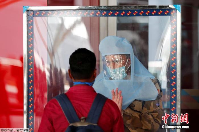 5月25日,在印度孟买希拉吉国际机场,安保人员核对旅客身份信息。 印度政府允许国内航线自5月25日起恢复。