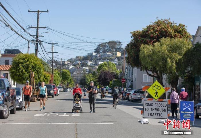 """当地时间5月24日,美国旧金山桑切斯路仅对自行车以及行人开放。在""""慢街道""""计划实施之后,旧金山又关闭了更多街道的汽车通行权,以保障市民有更多的空间保持""""社交距离""""。中新社记者 刘关关 摄"""