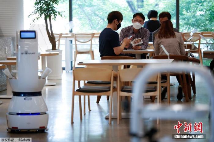 """当地时间5月25日,韩国大田,当地一家咖啡馆""""雇佣""""机器人服务员,这款机器人可以接受订单,制作咖啡,并将咖啡直接送到顾客的座位上。"""