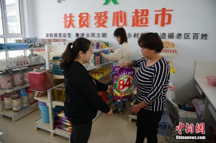 内蒙古乡村多种措施帮助贫困户,5月25日,在村中的扶贫爱心超市内,村民可根据文明积分兑换生活用品。记者 刘文华 摄