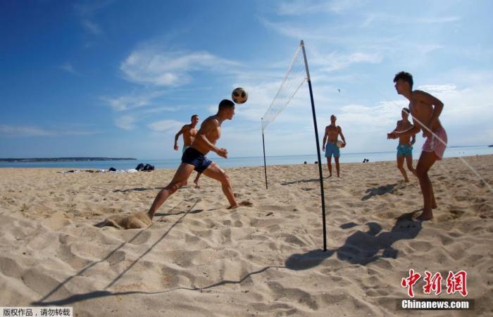 当地时间5月25日,民众在西班牙大加那利岛重新开放的海滩上玩乐休闲。据报道,随着疫情缓解,西班牙逐步放宽限制措施,一些省份放宽了解封第二阶段的一些限制。图为民众在沙滩上玩网式足球。