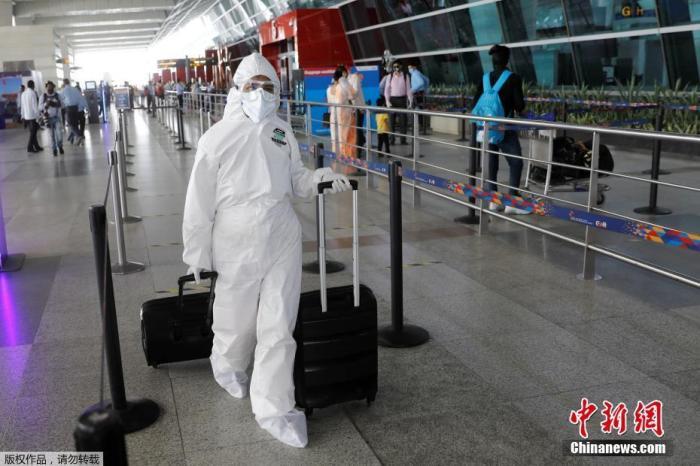 5月25日,在印度新德里英迪拉·甘地国际机场,旅客们穿戴着防护服和面罩出行。 印度政府允许国内航线自5月25日起恢复。