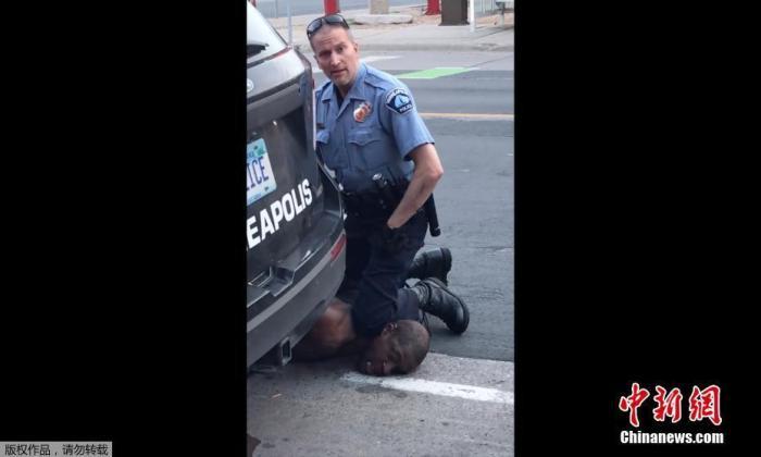 当地时间5月25日,美国明尼苏达州明尼阿波利斯市一名警察在逮捕非裔男子乔治・弗洛伊德时,将其按在地上,用膝盖顶住脖子。据目击者介绍,弗洛伊德被按到在地时反复在说自己无法呼吸后疑似陷入昏迷。随后弗洛伊德在被送往医院后不治身亡。(视频截图)