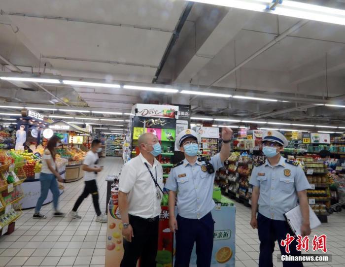 据武汉市新冠肺炎疫情防控指挥部消息,截至5月23日,该市重点大型商超和餐饮协会会员餐饮企业共5.58万人完成了核酸检测工作。近日,在做好疫情防控常态化同时,武汉各大商超和部分餐饮门店已逐步开放,客流量有序恢复。图为消防监督员正在检查超市内的消防安全设施设备是否完好有效。王方 摄