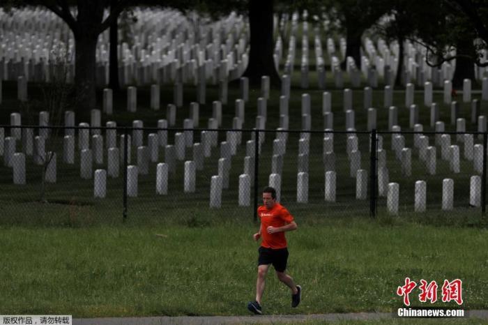 5月28日消息,约翰斯·霍普金斯大学实时统计数据显示,截至美东时间27日晚,美国新冠死亡病例已经超过10万例,但这场危机几乎仍未显示出缓和的迹象。图为当地时间5月27日,一名男子跑步途径美国弗吉尼亚州阿灵顿市阿灵顿国家公墓外。