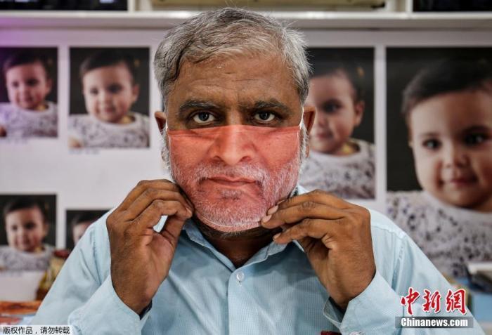 资料图:印度为民众定制符合个人脸部特征的口罩,一名顾客拿到了自己的口罩进行试戴。