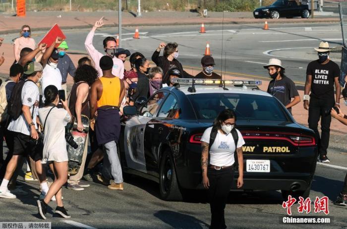 当地时间5月27日,美国洛杉矶市中心,抗议者在围住了一辆巡逻的警车。