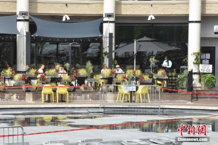 """当地时间5月29日,美国首都华盛顿正式""""解封"""",包括餐厅室外座位、理发店、公园等""""开门""""。图为民众在餐厅室外座位保持""""社交距离""""用餐。 lt;a target='_blank' href='http://www.chinanews.com/'gt;郑州资讯lt;/agt;记者 沙晗汀 摄"""