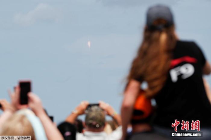 """當地時間5月30日,美國宇航局(NASA)商業載人航空計劃(CPP)的首次載人試航發射成功。據報道,美國宇航員道格拉斯·赫爾利(道格)和羅伯特·本肯(鮑勃)搭乘美國太空探索技術公司(SpaceX)的載人""""龍""""飛船,由""""獵鷹9""""火箭于從佛羅里達州肯尼迪航天中心39A發射臺升入太空,并計劃于美東時間5月31日下午2時27分與國際空間站對接。圖為美國民眾圍觀火箭升空。"""