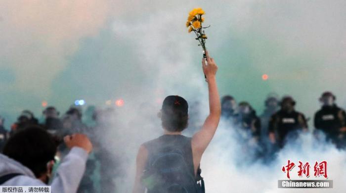 当地时间5月30日,美国明尼苏达州明尼阿波利斯市实施宵禁后,当地警方仍在和抗议民众对峙。