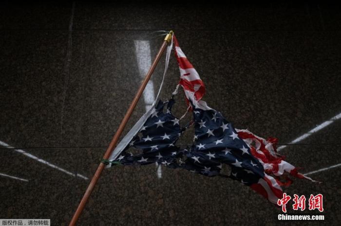 当地时间5月30日,美国密歇根州底特律,一面颠倒悬挂美国国旗被遗弃在抗议示威后的街道上。
