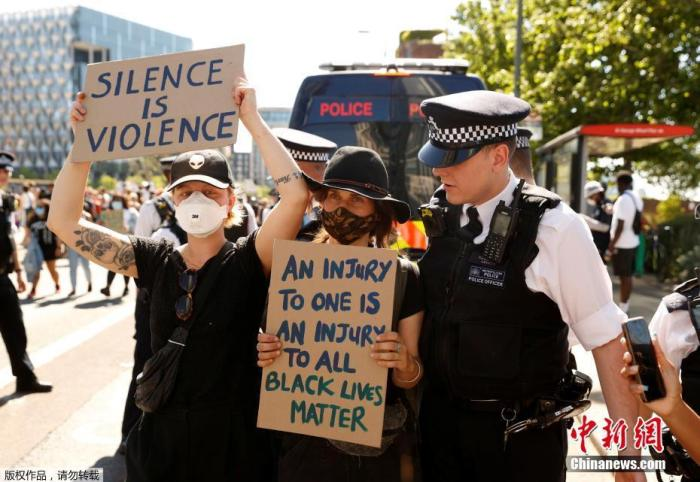 5月31日,英國倫敦,當地警察站在手持標語的抗議者身前。