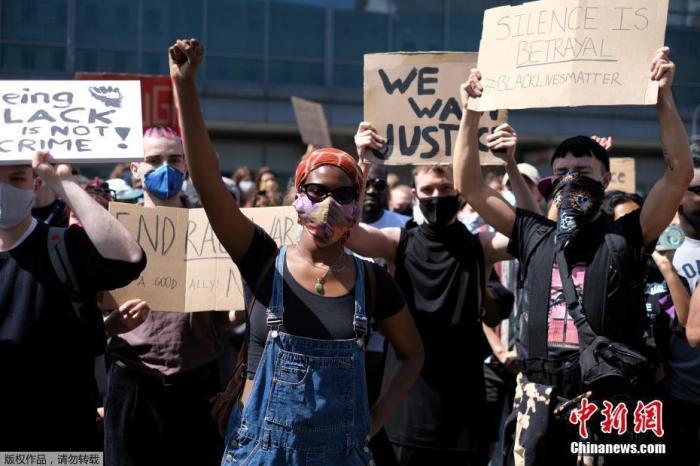5月31日,德国柏林纽科伦区赫尔曼普拉茨广场,民众带着口罩手举标语进行抗议示威活动。