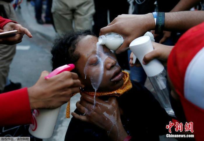 当地时间5月31日,美国华盛顿白宫附近的拉斐特公园的抗议活动中,抗议者们为受胡椒喷雾剂影响的妇女清洗眼部。