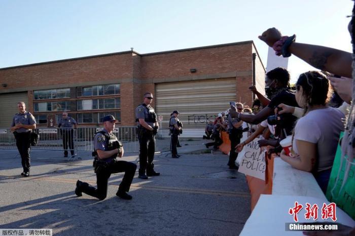 当地时间5月31日,美国俄克拉荷马市警察局外,一名警察单膝跪地声援抗议者。