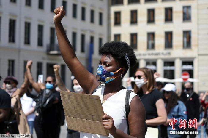 当地时间5月31日,德国柏林美国驻德国大使馆外,聚集在此进行抗议的人们举起拳头示威。