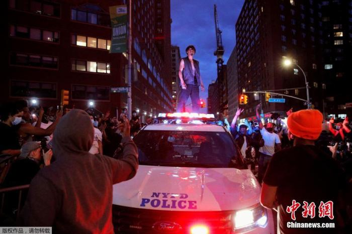 当地时间5月30日,美国纽约曼哈顿联合广场上,示威者站在受损的纽约警车上。