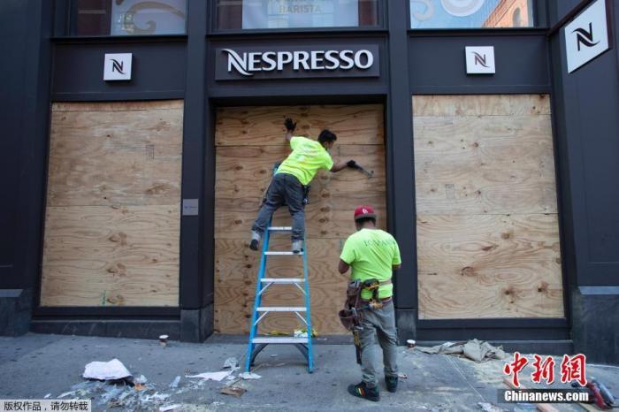应对示威中的暴力,纽约市决定实施宵禁。图为 当地时间6月1日,美国纽约,工人对一家店铺的橱窗进行加固。