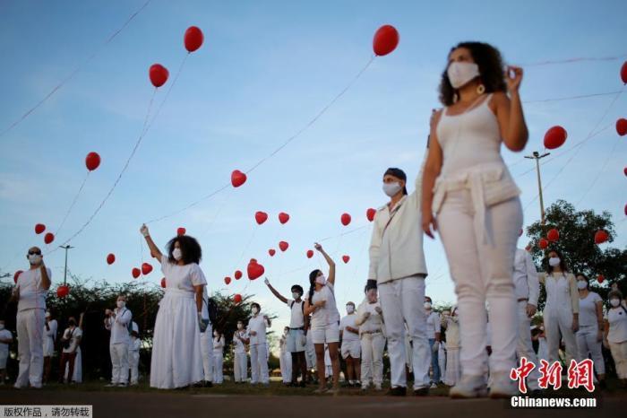 当地时间6月1日,巴西首都巴西利亚,艺术家们手持红色气球悼念在新冠疫情中不幸离世的人们。