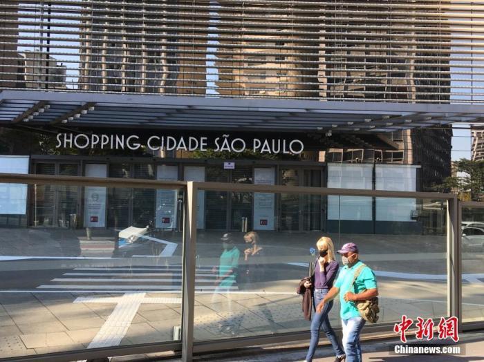 原料图:当地时间6月1日,在巴西圣保罗,两名走人从一家关闭的大型购物中央前走过。 中新社记者 莫成雄 摄