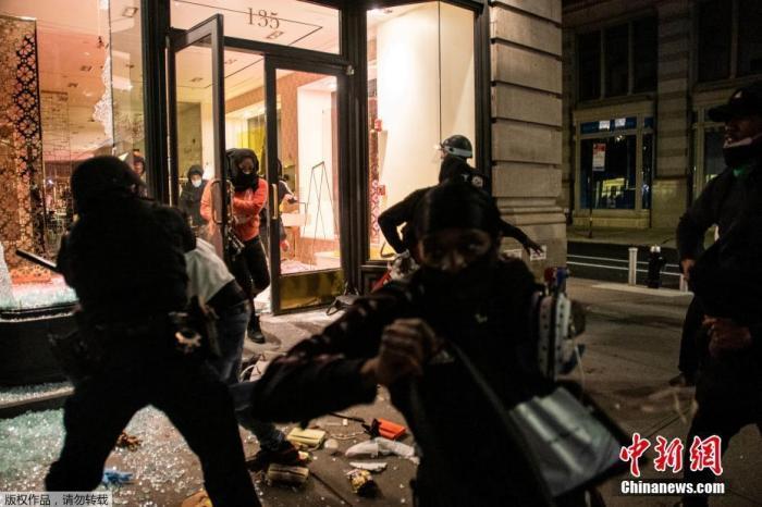 当地时间5月31日,美国纽约曼哈顿区,示威者从被砸毁的店铺中拿走奢侈品。