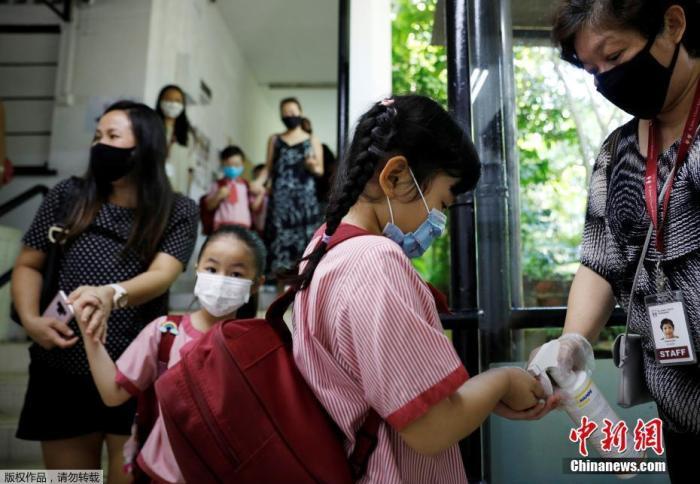 只有一些特定人群仍可获准戴面罩,包括难以长时间戴着口罩的12岁及以下孩童,以及因健康状况不适合长时间戴口罩,否则或会引起呼吸困难或其他症状的人。在教室或讲座场合面向人群授课者,若主要站在同个位置发言,并且能与其他人保持安全距离,也可继续戴面罩。图为当地时间6月2日,新加坡校重新开学,幼儿园学生进教室前用洗手液消毒。