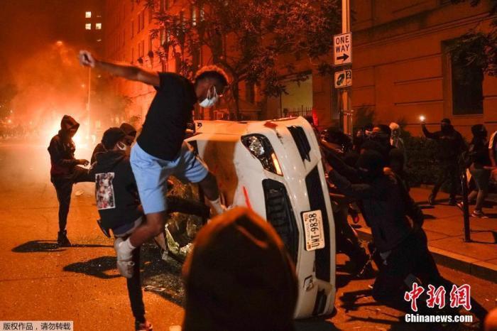 资料图:在美国首都华盛顿白宫附近,示威者将警车推翻砸烂。